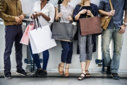 An image of people standing with shopping bags