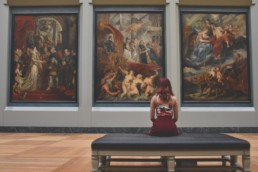 An image of a woman sitting in the art gallery looking at art.
